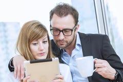 Compañeros de trabajo jovenes que miran el dispositivo de la tableta Fotografía de archivo libre de regalías