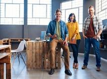 Compañeros de trabajo jovenes sonrientes en el trabajo junto en una oficina moderna Fotos de archivo