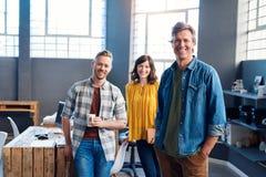 Compañeros de trabajo jovenes sonrientes que se unen en una oficina moderna Foto de archivo libre de regalías