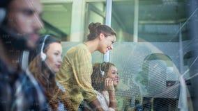 Compañeros de trabajo de la mujer que trabajan en Callcenter