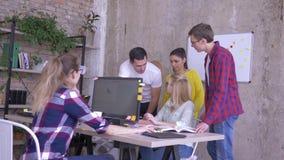 Compañeros de trabajo de la oficina que se colocan en la tabla con el ordenador portátil que discute el plan empresarial e ideas  almacen de video