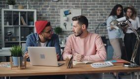Compañeros de trabajo de los individuos que hablan mirando la pantalla del ordenador portátil que trabaja en oficina junto metrajes