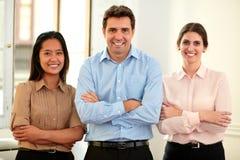 Compañeros de trabajo masculinos y femeninos que cruzan los brazos Foto de archivo libre de regalías