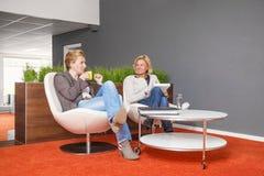 Compañeros de trabajo que beben el café en la oficina imagen de archivo