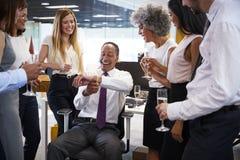 Compañeros de trabajo que celebran un retiro del ½ s del ¿del colleagueï en la oficina fotografía de archivo