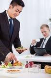 Compañeros de trabajo que comen el almuerzo durante la reunión imagen de archivo