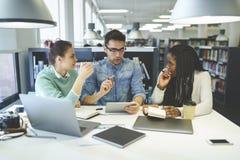 Compañeros de trabajo que discuten proyecto de inicio mientras que comprueba la información usando los dispositivos y la conexión imagen de archivo libre de regalías