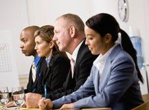 Compañeros de trabajo que escuchan durante la reunión Fotos de archivo