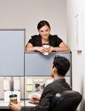 Compañeros de trabajo que hablan en cubículo de la oficina fotografía de archivo