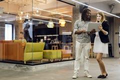 Compañeros de trabajo que hablan en una oficina moderna Imágenes de archivo libres de regalías