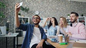 Compañeros de trabajo que hacen la llamada video con el smartphone que habla y que gesticula en oficina almacen de metraje de vídeo