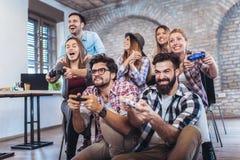 Compañeros de trabajo que juegan a los videojuegos imagenes de archivo