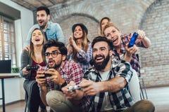 Compañeros de trabajo que juegan a los videojuegos imagen de archivo