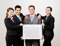 Compañeros de trabajo que llevan a cabo la línea gráfico financiera Foto de archivo