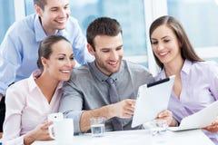 Compañeros de trabajo que miran la tableta digital Foto de archivo