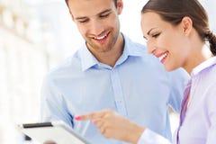 Compañeros de trabajo que miran la tableta digital Foto de archivo libre de regalías