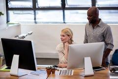 Compañeros de trabajo que miran un ordenador Imágenes de archivo libres de regalías