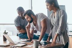 Compañeros de trabajo que miran un ordenador portátil y que lo discuten sobre nuevo plan empresarial Equipo del negocio que traba foto de archivo
