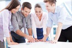 Compañeros de trabajo que se inclinan sobre la tabla Imágenes de archivo libres de regalías