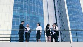 Compañeros de trabajo que tienen una reunión al aire libre que toma tiempo apagado metrajes