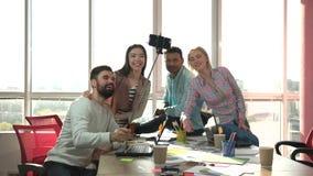 Compañeros de trabajo que toman el palillo del selfie del usind de la foto y que juegan el mono
