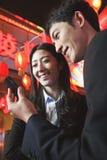Compañeros de trabajo que usan el teléfono elegante en la noche, calle de la ciudad, linternas rojas en el fondo Foto de archivo libre de regalías