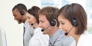 Compañeros de trabajo serios con el receptor de cabeza encendido Foto de archivo libre de regalías