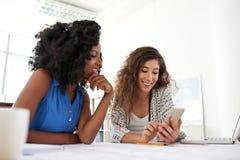 Compañeros de trabajo sonrientes con Smartphone imagen de archivo libre de regalías