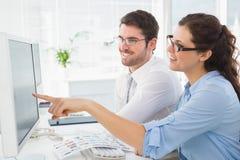 Compañeros de trabajo sonrientes del negocio que señalan la pantalla del ordenador Foto de archivo libre de regalías