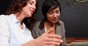 Compañeros de trabajo sonrientes que usan la tableta almacen de metraje de vídeo