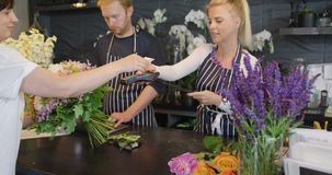 Compañeros de trabajo y cliente en tienda floral almacen de video