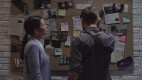 Compañeros felices que dan cinco cerca del tablero en la oficina de policía, explicación del hallazgo almacen de metraje de vídeo