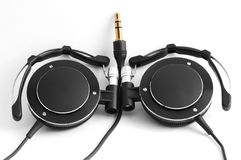 Compact black headphones. With gold jack on white Royalty Free Stock Photography