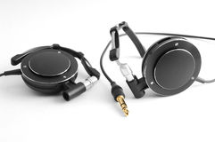 Compact black headphones. With gold jack on white Stock Photography
