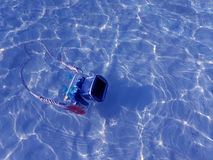 Compact camera and housing floating on the sea. Royalty Free Stock Image