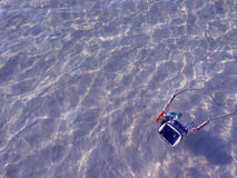 Compact camera and housing floating on the sea. Royalty Free Stock Photos
