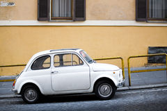 Compact car on Italian street. Compact car parked on a small uphill Italian street Royalty Free Stock Photos