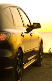 Compact Car near the Shore. A small, black, compact car on beach at sunset Royalty Free Stock Image