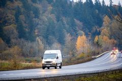 Compact cargo mini van for small business and local delivery driving in winding wet autumn road in rain weather. White popular compact cargo mini van comfortable royalty free stock photography