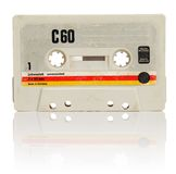 Compact Cassette. Vintage compact cassette audio tape on white with natural reflection Royalty Free Stock Photo