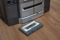 Compact cassette and audio tape player on table wood background stock images