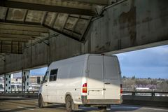 Commercial cargo mini van running on the two level bridge. Compact commercial transportation economical, convenient minivan for small business or local moving stock images
