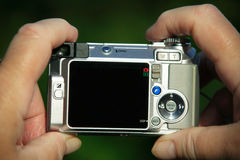 Compact digital camera. Amateur photographer focusing a silver compact digital camera Royalty Free Stock Photos