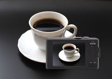 Compact digital camera photographed cup of coffee. Compact digital camera photographed white cup with coffee Stock Photo