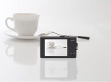 Compact digital camera photographed white cup. With spoon and saucer. Below blurred reflection Stock Photos