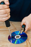 Compact disc being destroyed. Man destroying a compact disc with a screwdriver Stock Photo
