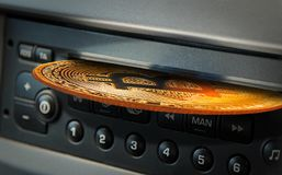 Compact disc bitcoin. Photo of a gold bitcoin cryptocurrency compact disc being inserted into a digital music player concept Stock Photography