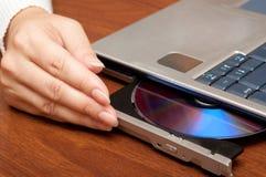 Compact disc sul computer portatile Fotografia Stock Libera da Diritti