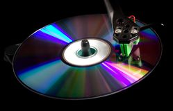 Compact disk concept. Tonearm of vinyl player on compact disk stock images
