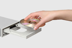 Compact disk drive. Female hand inserting a CD into a compact disk drive royalty free stock photos